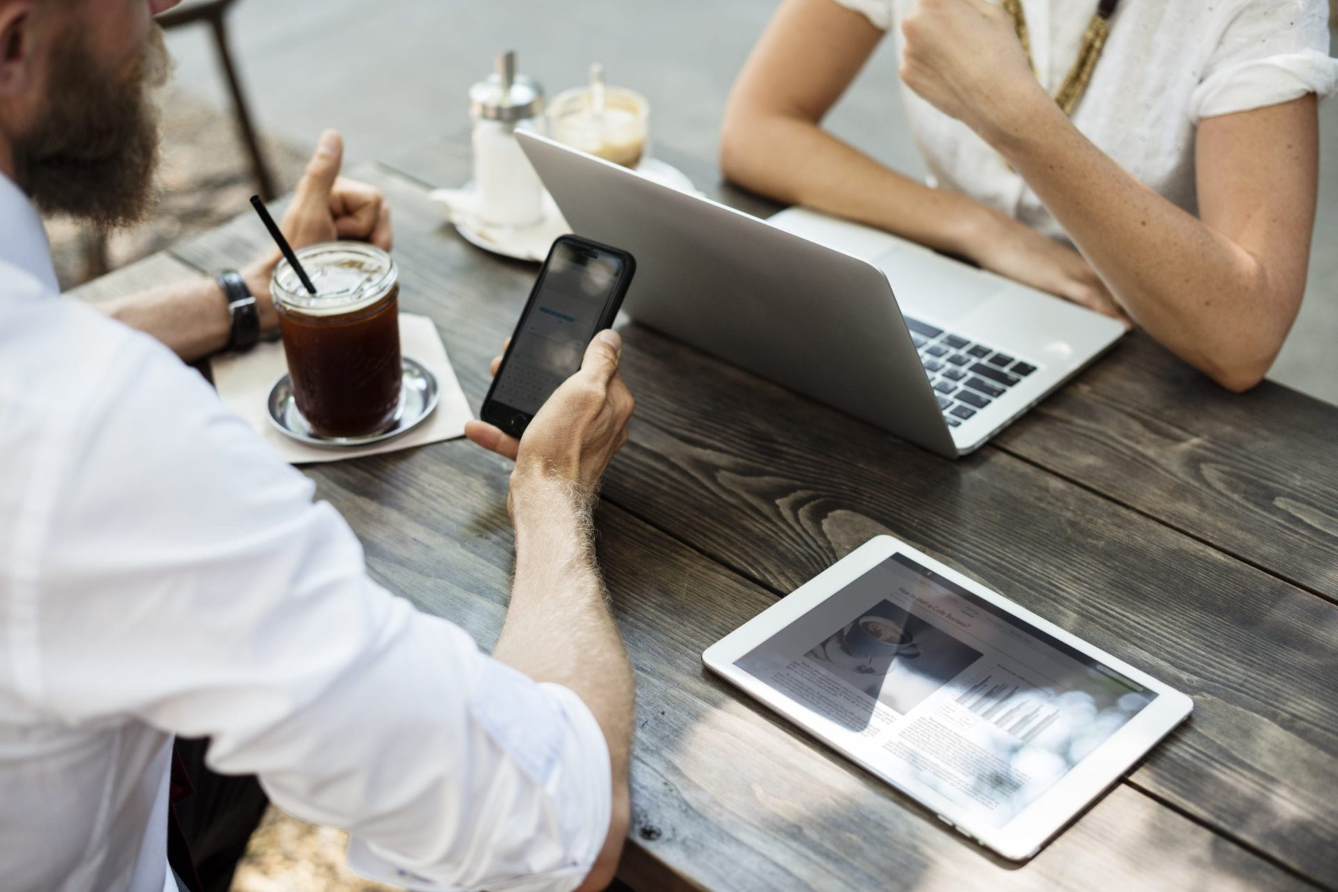 An image of two people working from various devices