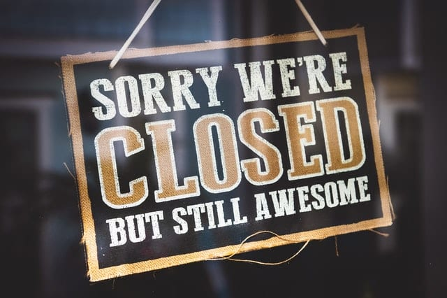 Closed sign hung on a door representing the government shutdown.